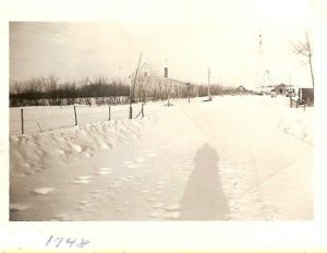 Haultain, Wetaskiwin farm home to the Humbke family of 12 plus windmill, building and car on a winter day in 1948.